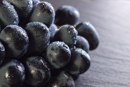 fresh ripe black grapes with drops of water on dark slate background, closeup macro. Stockfoto - 99050252