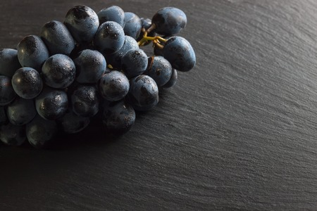 fresh ripe black grapes on dark slate background, top view with copy space. Stockfoto - 99155186