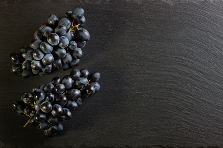 two branches of fresh ripe black grapes on dark slate background, top view with copy space. Stockfoto - 99029310