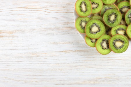 Slice of fresh kiwi fruit on the plate on white wooden background. top view.