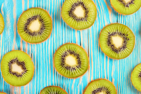 Slice of fresh kiwi fruit on blue wooden background. top view.