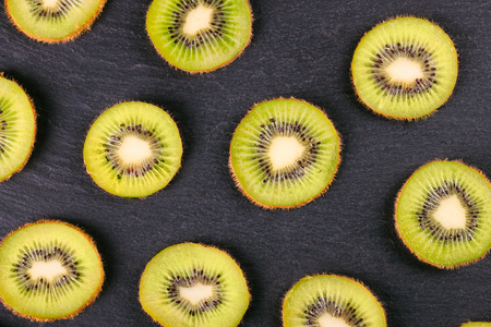 Slice of fresh kiwi fruit on black slate background. top view. Stockfoto - 101097410
