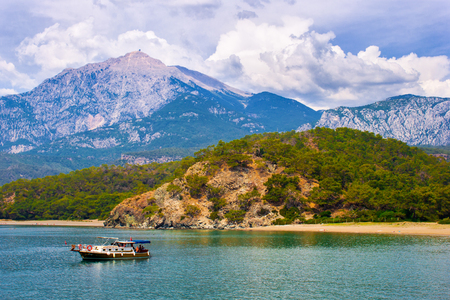 beautiful seascape. summer day in a bay with mountains and fantastic sky and a boat. Turkey. Antalya.