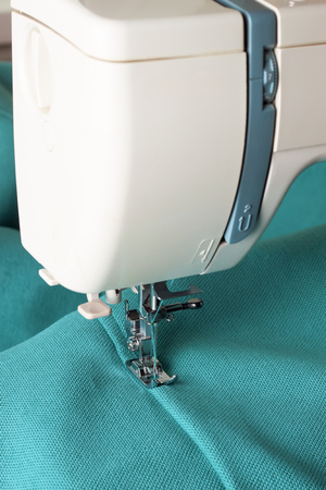 Sewing machine with turquoise fabric and thread, closeup