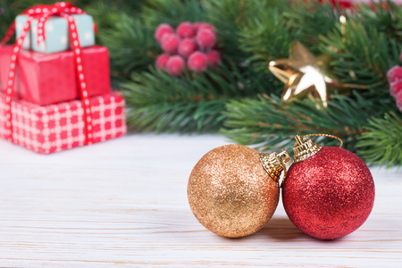 Christmas and new year composition. Christmas decorations, fir tree branch. Two balls on white wooden surface with fir branch backghound. small depth of field