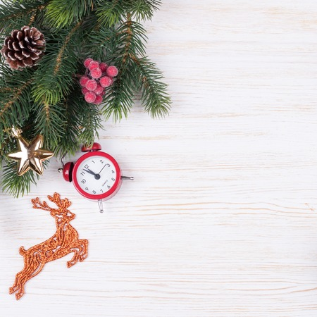 Christmas and new year composition. Christmas decorations, fir tree branch, garland, red santa claus hat, clock, gift on white wooden background. Flat lay, top view, copy space.