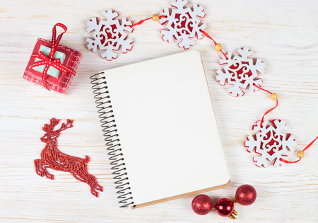 Christmas and new year composition. Christmas decorations, garland, clock, deer, gift and blank notebook on white wooden background. Flat lay, top view, copy space. Banco de Imagens