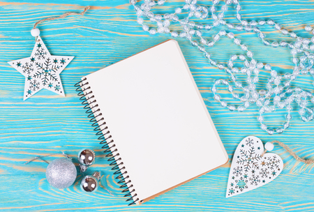 Christmas and new year composition. Christmas decorations, garland, balls and blank notebook on blue wooden background. Flat lay, top view, copy space. Stockfoto