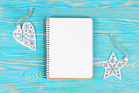 Christmas and new year composition. Christmas decorations, and blank notebook on blue wooden background. Flat lay, top view, copy space.