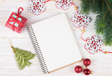 Christmas and new year composition. Christmas decorations, garland, clock, gift and blank notebook on white wooden background. Flat lay, top view, copy space.