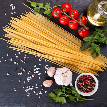 Ingredients for italian pasta. Spaghetti, tomatoes, oil, onion, garlic, spice on black slate background. Flat lay, top view.