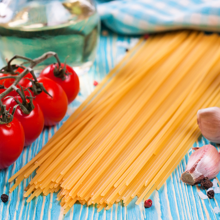 Ingredients for italian pasta. Spaghetti, tomatoes, oil, onion, garlic, spice on blue wooden background. shallow depth of field