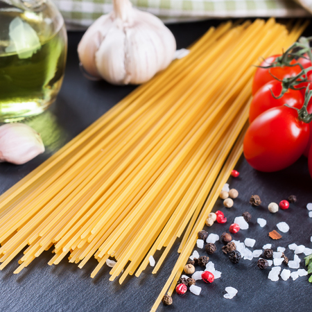 Ingredients for italian pasta. Spaghetti, tomatoes, oil, onion, garlic, spice on black slate background. shallow depth of field