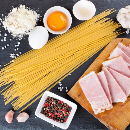 Ingredients for italian pasta carbonara . Spaghetti, egg, garlic, spice,parmesan, bacon on black slate background. Flat lay , top view.