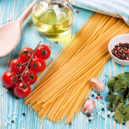 Ingredients for italian pasta. Spaghetti, tomatoes, oil, onion, garlic, spice on blue wooden background. Flat lay, top view.