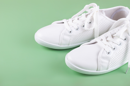 white female sneakers on green background with copy space.