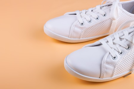 white female sneakers on pink background with copy space.