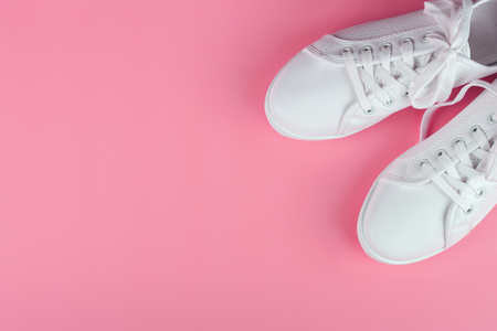 white female sneakers on pink background with copy space. top view, flat lay. 写真素材