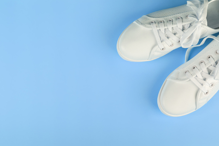 white female sneakers on blue background with copy space. top view, flat lay.