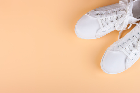white female sneakers on coral background with copy space. top view, flat lay.