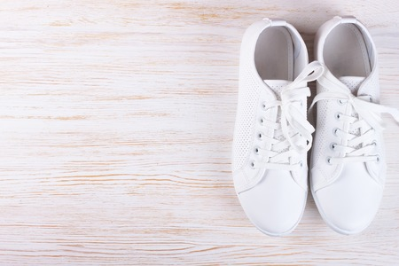 white female sneakers on white wooden background with copy space. top view, flat lay.