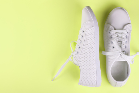 white female sneakers on yellow background with copy space. top view, flat lay.