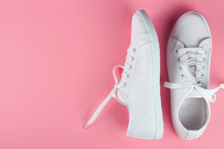 white female sneakers on pink background with copy space. top view, flat lay. Stockfoto