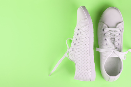 white female sneakers on green background with copy space. top view, flat lay.