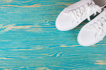 white female sneakers on blue wooden background with copy space. top view, flat lay.