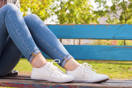White sneakers on female legs in blue jeans on a blue bench and green plant background.