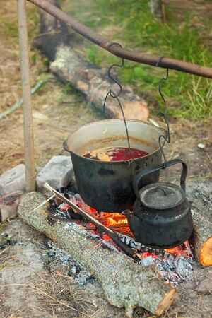 Two smoked tourist kettles over camp fire. Process of cooking on the nature. Banco de Imagens