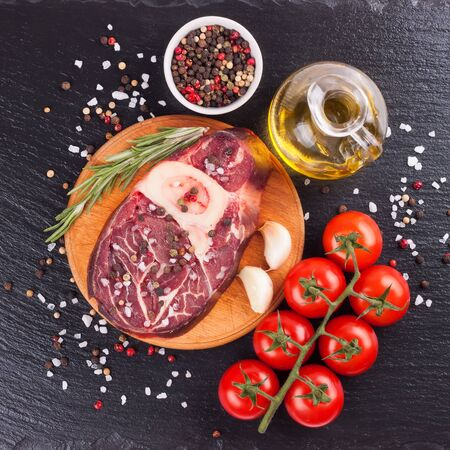 raw meat beef steak with bone, spices, rosemary and cooking ingredients on cutting board and black slate background. top view, flat lay.