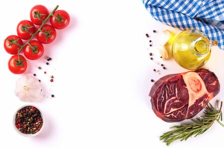 ingredients for cooking. raw beef steak with bone and spices, tomatoes, rosemary, garlic, olive oil isolated on a white background with copy space in the center. Top view, flat lay.