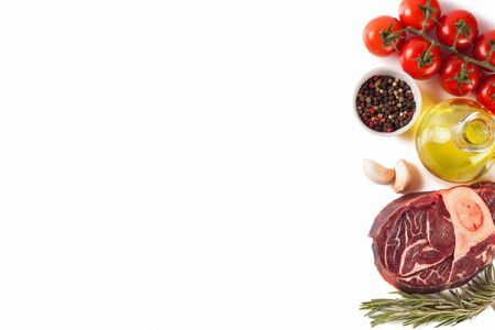 ingredients for cooking. raw beef steak with bone and spices, tomatoes, rosemary, garlic, olive oil isolated on a white background with copy space. Top view, flat lay. Zdjęcie Seryjne