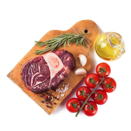 Fresh raw meat beef steak with bone with spices, rosemary, tomatoes, garlic and olive oil on wooden cutting board isolated on white background. Top view. Flat lay. 写真素材