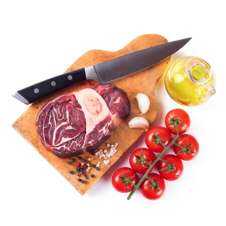 Fresh raw meat beef steak with bone with spices, rosemary, tomatoes, garlic and olive oil on wooden cutting board with kitchen knife isolated on white background. Top view. Flat lay.