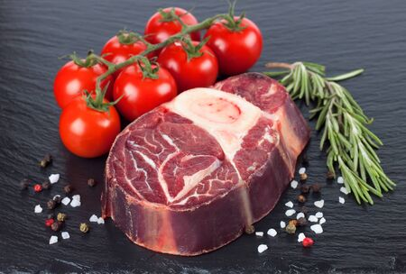 Fresh raw meat beef steak with bone with spices, rosemary and tomatoes on the black slate surface. raw cooking ingredients