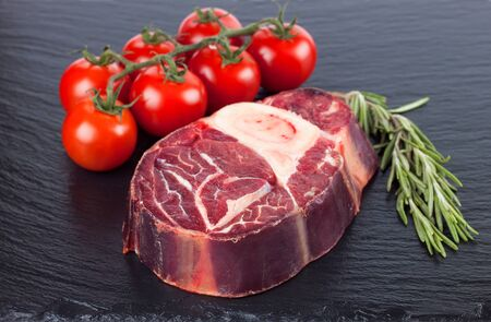 Fresh raw meat beef steak with bone , rosemary and tomatoes on the black slate surface. raw cooking ingredients