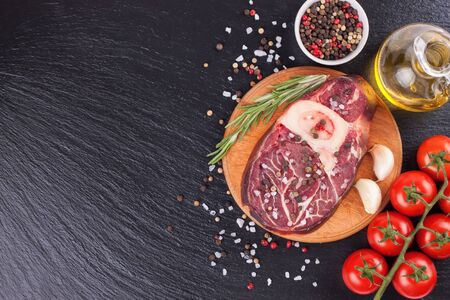 Fresh raw meat beef steak with bone with spices, rosemary, tomatoes, garlic and olive oil on wooden cutting board and on the black slate surface. cooking ingredients. Top view. Flat lay.