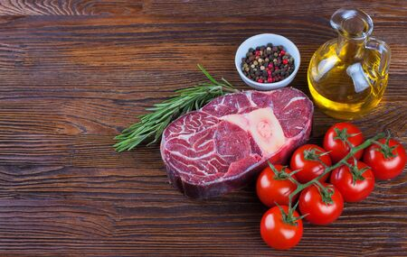 Fresh raw meat beef steak with bone with spices, rosemary, tomatoes and olive oil on brown wooden background. cooking ingredients.