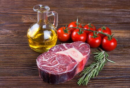 Fresh raw meat beef steak with bone with rosemary, tomatoes and olive oil on brown wooden background. cooking ingredients. Stockfoto