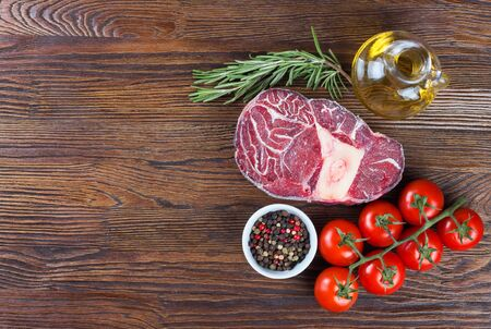 Fresh raw meat beef steak with bone with spices, rosemary, tomatoes and olive oil on wooden background. cooking ingredients. Top view. Flat lay.