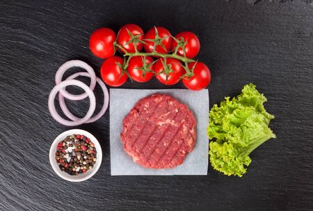 Fresh raw home-made minced beef steak burger with spices, tomatoes and salad on a black slate table, top view. Flat lay. Zdjęcie Seryjne