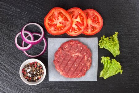 Fresh raw home-made minced beef steak burger with spices, tomatoes, salad and onion, on a black slate table, copy space, top view