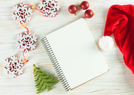 New Year background with Christmas decorations and empty note greeting card on white wooden surface. Top view. Stock Photo