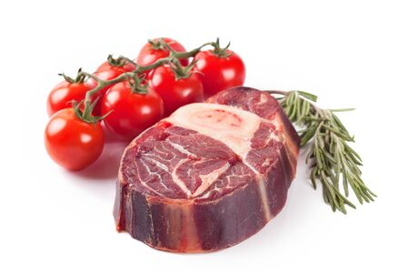 raw meat beef steak with bone, tomatoes and rosemary on white background.