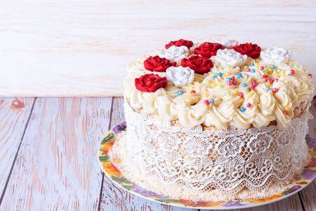white cake with cream and red roses on white wooden backghound.