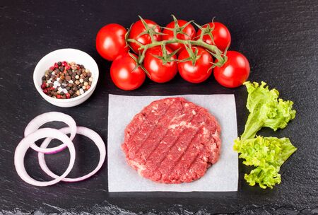 Fresh raw home-made minced beef steak burger with spices, tomatoes, onion and salad on a black slate table, top view. Flat lay. Stockfoto