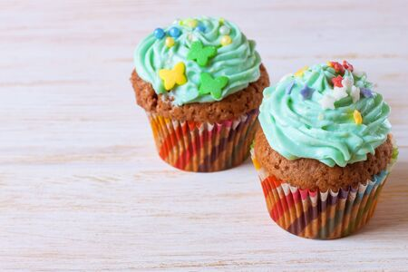 two colorful handmade cupcakes with green cream on a white wooden background. Stockfoto
