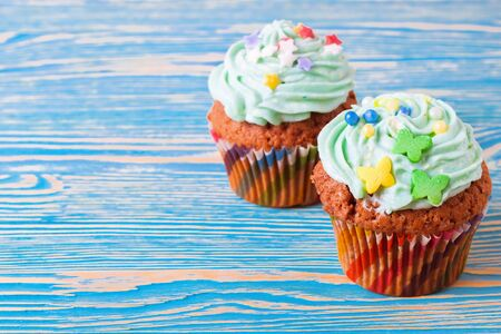 two colorful handmade cupcakes with green cream on a blue wooden background.